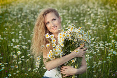 Beautiful lady with cute daughter on camomile field Stock Photography