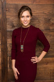 Beautiful lady in dark red dress. With hand on hip over wooden background. Happy lady smiling for the camera Stock Image