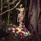 Beautiful lady in dress of flowers. Blooming gorgeous lady in a dress of flowers in the rainforest Stock Image