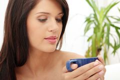 Beautiful lady is drinking coffee. At bed Royalty Free Stock Image