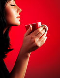 Beautiful lady drinking coffee. Brunette enjoy cup of hot chocolate, side view cute girl  on red background, portrait of female with morning tea, gorgeous Royalty Free Stock Photos