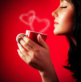 Beautiful lady drinking coffee. Brunette enjoy cup of hot chocolate, side view cute girl  on red background, portrait of female with morning tea, gorgeous Royalty Free Stock Images