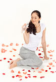 Beautiful lady drinking gas water. Young beautiful lady drinking gas water sitting on the floor covered with rose petals on white Royalty Free Stock Photo