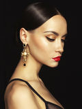Beautiful lady with earring on black background Stock Photos