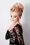 Beautiful lady in elegant black evening dress with updo hairstyle. Fashion photo. Royalty Free Stock Photography
