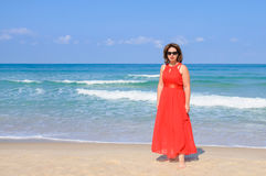 Beautiful lady in elegant red dress  at beach, with sea and blue Stock Photo