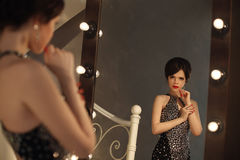 Beautiful lady in fashion dress posing by mirror with light bulb Royalty Free Stock Images