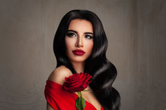 Beautiful Lady. Fashion Portrait of Perfect Woman. With Brunette Hair and Event Makeup. Curly Hairstyle, Red Lips, and Red Rose Flower Stock Image