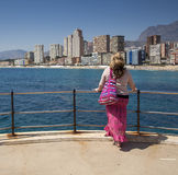 Beautiful lady gazes over Playa de Levante, Benidorm, Spain. Royalty Free Stock Image