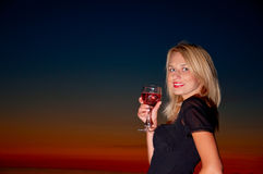 Beautiful lady with glass of wine on the beach. Beautiful lady i black dress with glass of wine on the beach stock photos