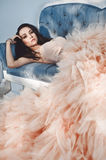 Beautiful lady in gorgeous couture dress on sofa Royalty Free Stock Photo