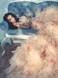 Beautiful lady in gorgeous couture dress on sofa Stock Images