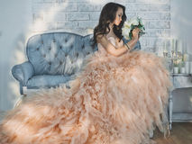 Beautiful lady in gorgeous couture dress on sofa Royalty Free Stock Photography