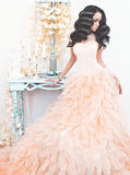 Beautiful lady in gorgeous couture dress in white interior Royalty Free Stock Image