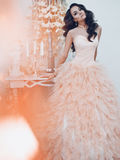 Beautiful lady in gorgeous couture dress in white interior Stock Image
