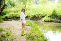 Beautiful lady in gumboots at river bank Royalty Free Stock Image