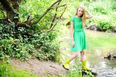 Beautiful lady in gumboots at river bank Royalty Free Stock Photo