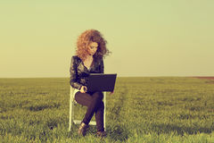 Beautiful lady with her laptop on grass stock photography