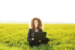 Beautiful lady with her laptop on grass Royalty Free Stock Photo