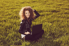 Beautiful lady with her laptop on grass Stock Image