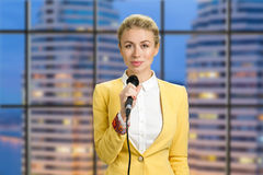 Beautiful lady holding microphone. Waist up portrait of elegant woman reporter standing on office evening background and smiling at camera royalty free stock images