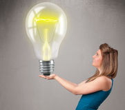 Beautiful lady holding realistic 3d light bulb Royalty Free Stock Image