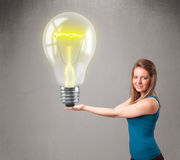 Beautiful lady holding realistic 3d light bulb Royalty Free Stock Photos