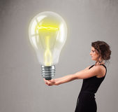 Beautiful lady holding realistic 3d light bulb Royalty Free Stock Photo