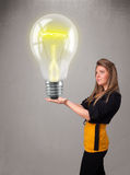 Beautiful lady holding realistic 3d light bulb Stock Image