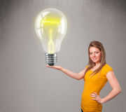 Beautiful lady holding realistic 3d light bulb Royalty Free Stock Photography