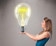 Beautiful lady holding realistic 3d light bulb Stock Images