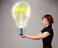 Beautiful lady holding realistic 3d light bulb Stock Photo