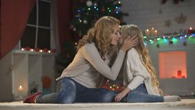 Beautiful lady kissing and hugging daughter, waiting Christmas eve celebration. Stock footage stock video