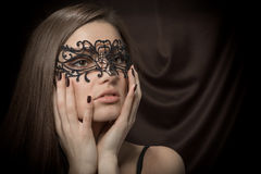 Beautiful lady in lacy black mask. Closeup portrait of beautiful lady in lacy black mask on dark brown background Stock Image