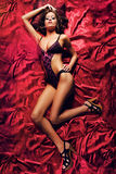 Beautiful lady laying down on red fabric. Royalty Free Stock Photography
