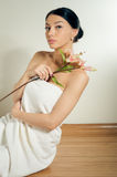 Beautiful lady with lilly flower. Perfect skin. Stock Image