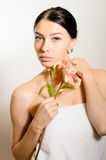 Beautiful lady with lilly flower. Perfect skin. Royalty Free Stock Image