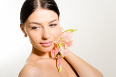 Beautiful lady with lilly flower. Perfect skin. Royalty Free Stock Images