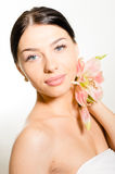 Beautiful lady with lilly flower. Perfect skin. royalty free stock photo