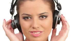 Beautiful lady listening music in large headphones, looking at camera and making blow kisses stock video footage