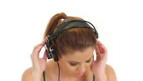 Beautiful lady listening music in large headphones, looking at camera and making blow kisses stock footage