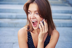 Beautiful lady listening to her phone interlocuter with the surp. Beautiful lady is listening to her phone interlocuter with the surprised expression on her face Stock Photos