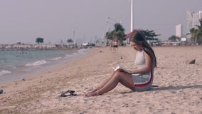 Beautiful lady with long dark hair reads book on sand beach. Against green palms and modern hotel buildings stock footage