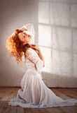 Beautiful lady with long wavy red hair in kneeling pose Stock Photos