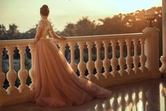 Beautiful lady in luxurious ballroom dress with tulle skirt and lacy top standing on the large balcony. Looking away at sunset. Back view. Text space royalty free stock photos
