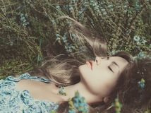 Beautiful lady lying amond flowers Royalty Free Stock Photos