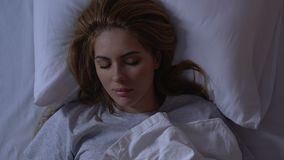 Beautiful lady lying in bed at night, cozy healthy sleep on comfortable mattress