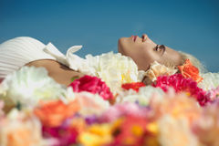 Beautiful lady lying in flowers Royalty Free Stock Images