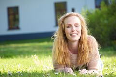 Beautiful lady lying on grass outdoors Stock Images