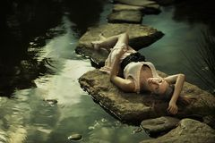 Beautiful lady lying on rocks Stock Photo